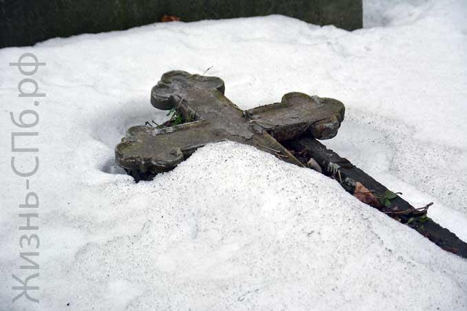 Крест в снегу на смоленском Лютеранском кладбище